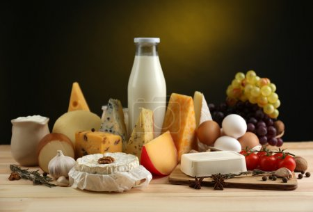 Photo for Tasty dairy products on wooden table, on dark background - Royalty Free Image