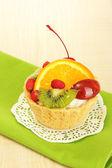 Sladký dort s ovocem na dřevěný stůl
