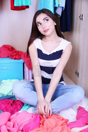 Beautiful young woman sitting on floor near wardrobe in room