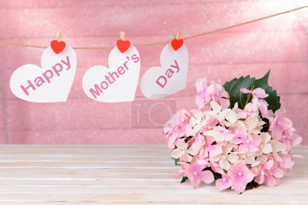 Photo for Happy Mothers Day message written on paper hearts with flowers on pink background - Royalty Free Image
