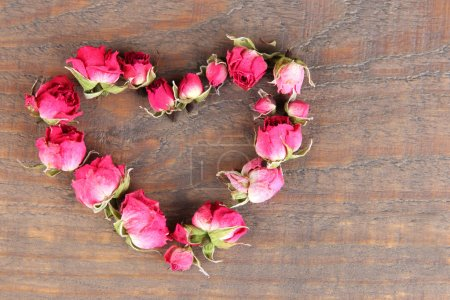Photo for Heart of beautiful pink dried roses on old wooden background - Royalty Free Image