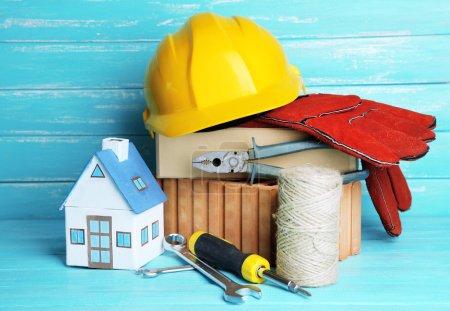 Photo pour Composition avec casque de sécurité, gants en cuir, outils et maison décorative sur fond en bois - image libre de droit