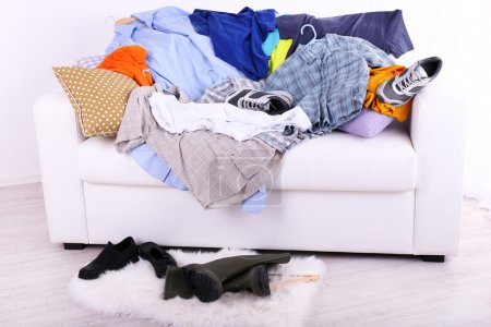 Photo for Messy colorful male clothing on  sofa on light background - Royalty Free Image
