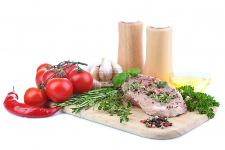 Raw meat steak with herbs and spices on cutting board, isolated on white