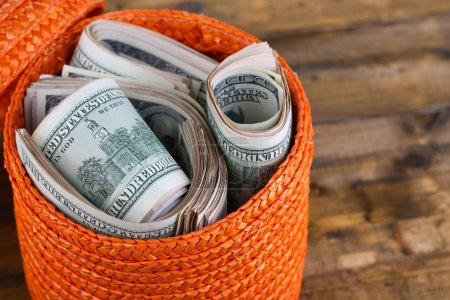 Photo for Packs of dollars stored in basket on wooden table - Royalty Free Image