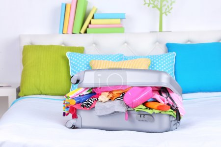 Photo for Grey suitcase with clothing on bed close-up - Royalty Free Image