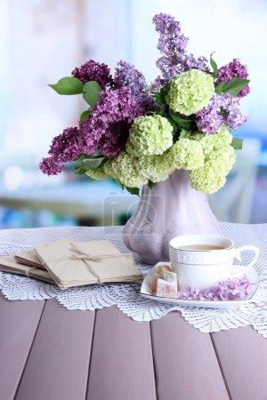 Foto de Composición con taza de té, cartas viejas y hermosa primavera flores en florero, sobre mesa de madera, sobre fondo brillante - Imagen libre de derechos