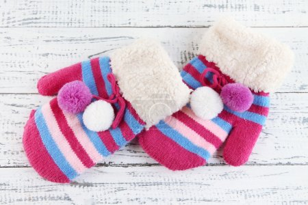 Photo for Striped mittens on wooden background - Royalty Free Image