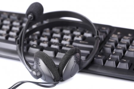 Headphone and keyboard, close-up, isolated on white