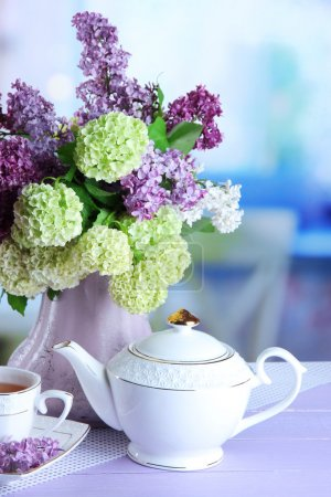 Composition with teapot,  mug and beautiful spring flowers in vase, on wooden table, on bright background