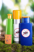 Bottles with mosquito repellent cream on nature background