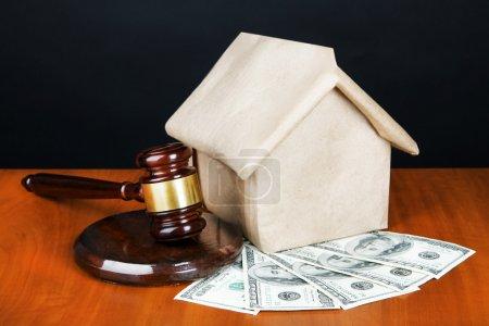 Photo pour Coup de marteau, modèle de maison et de l'argent sur la table sur fond noir - image libre de droit