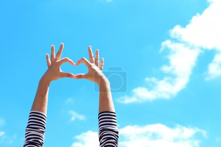Photo for Young girl holding hands in heart shape framing on blue sky background - Royalty Free Image
