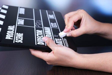 Black cinema clapper board in hands