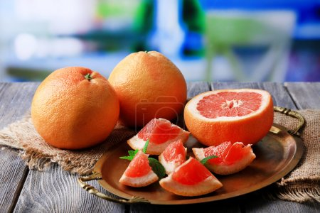 Ripe grapefruits on tray, on wooden table, on bright background