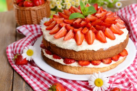 Photo for Delicious biscuit cake with strawberries on table close-up - Royalty Free Image