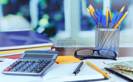 Photo pour Fournitures de bureau avec des documents et de l'argent sur la table sur fond lumineux - image libre de droit