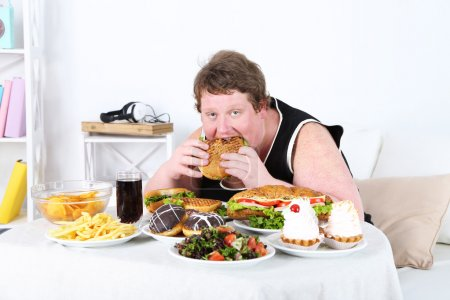 Fat man eating a lot of unhealthy food, on home in...