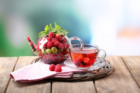 Photo for Fruit red tea with wild berries in glass cup, on wooden table, on bright background - Royalty Free Image