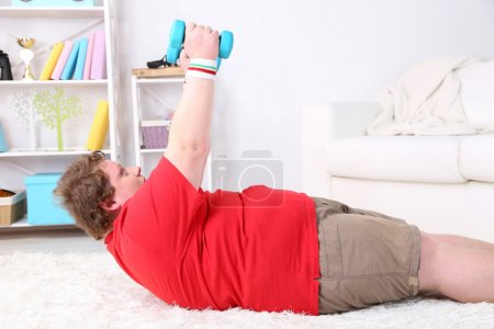 Grand fitness homme faire des exercices avec haltères sur le sol, à la maison