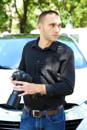 Man near car with photo camera