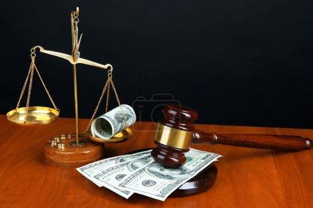 Photo pour Marteau, de balances et de l'argent sur la table sur fond noir - image libre de droit