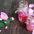Rose oil in bottles on color wooden background...