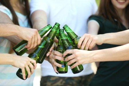 Hands holding beer bottles close up