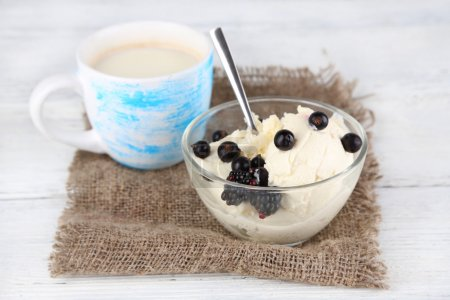 Cup of milk and cottage cheese in glass bowl on wooden background