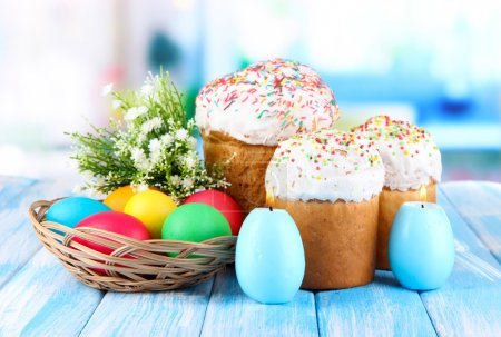 Photo for Sweet Easter cakes with colorful eggs on table in room - Royalty Free Image