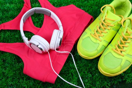 Photo for Sport clothes, shoes and headphones on green grass background - Royalty Free Image