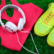 Sport clothes, shoes and headphones on green grass...