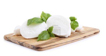 schmackhafter Mozzarella mit Basilikum auf Holzbrett isoliert auf weiß