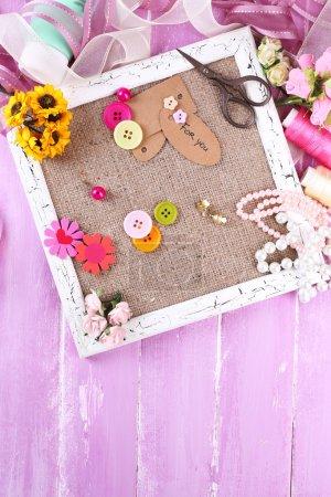 Photo pour Scrapbooking matériaux artisanaux et cadre en bois avec sac à l'intérieur sur fond en bois de couleur - image libre de droit