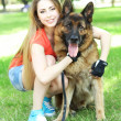 Beautiful young girl with dog in park...