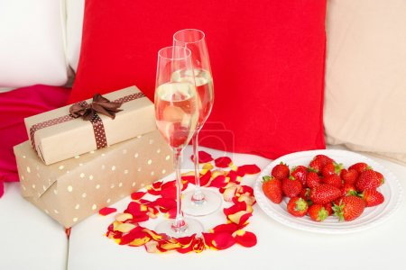 Romantic still life with champagne, strawberry and petals of roses on sofa