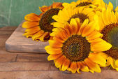 Beautiful sunflowers on table on wooden background