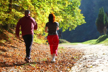 Photo for Woman and man walking cross country and trail in autumn forest - Royalty Free Image