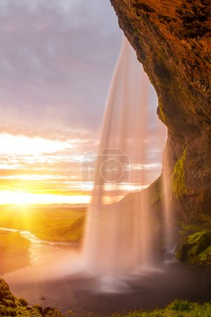 Photo for Seljalandsfoss is one of the most beautiful waterfalls on the Iceland. It is located on the South of the island. This photo is taken during the incredible sunset at approx. 1 AM. - Royalty Free Image