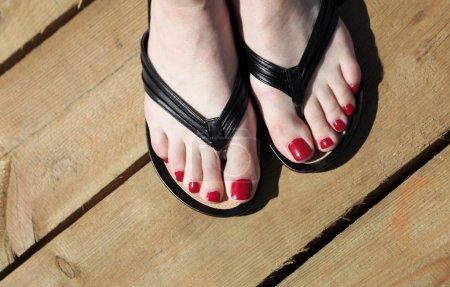 Photo pour Pieds féminins avec tongs clou rouge extérieur - image libre de droit