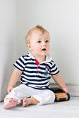 Malý chlapec sedí na podlaze s hračku stroj