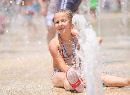 cute girl enjoying the fountains on a hot day