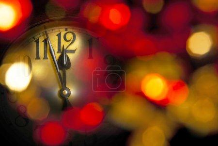Foto de Un año nuevo reloj con fondo desenfocado oscuro - Imagen libre de derechos