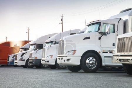Photo pour Différents camions américains dans une rangée avec un qui vient de commencer son voyage - image libre de droit