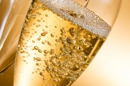 Photo for Empty glasses of champagne and one being filled against golden background - Royalty Free Image