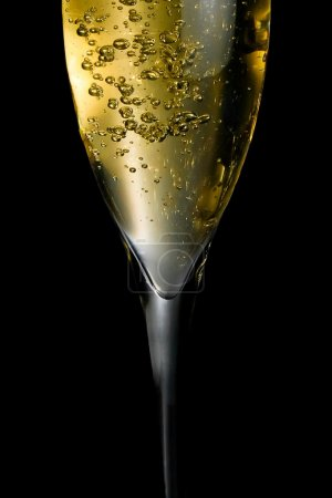 Photo for Champagne flute with golden fine bubbles on black background - Royalty Free Image
