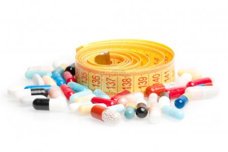 measuring tape with pills for dieting around