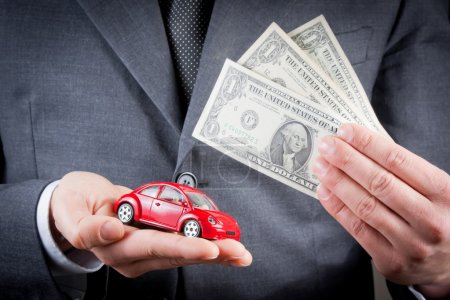 toy car and dollars in the hands of business man concept for insurance, buying, renting, fuel or service and repair costs
