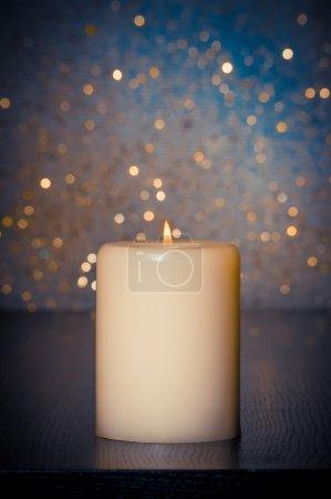 Photo pour Bougie avec flamme sur table en bois et fond bleu bokeh et espace pour le texte - image libre de droit