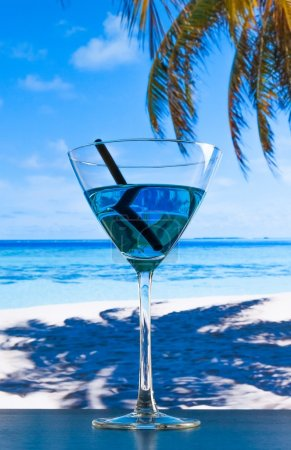 blue cocktail on beach on wood table